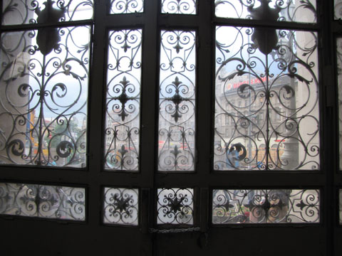 The city seen through the dirty glass of the station's gates